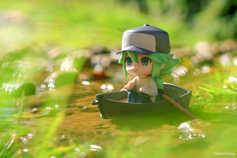 Toy photography by CuriousHerring of N nedoroid from Pokemon, in a boat on the water