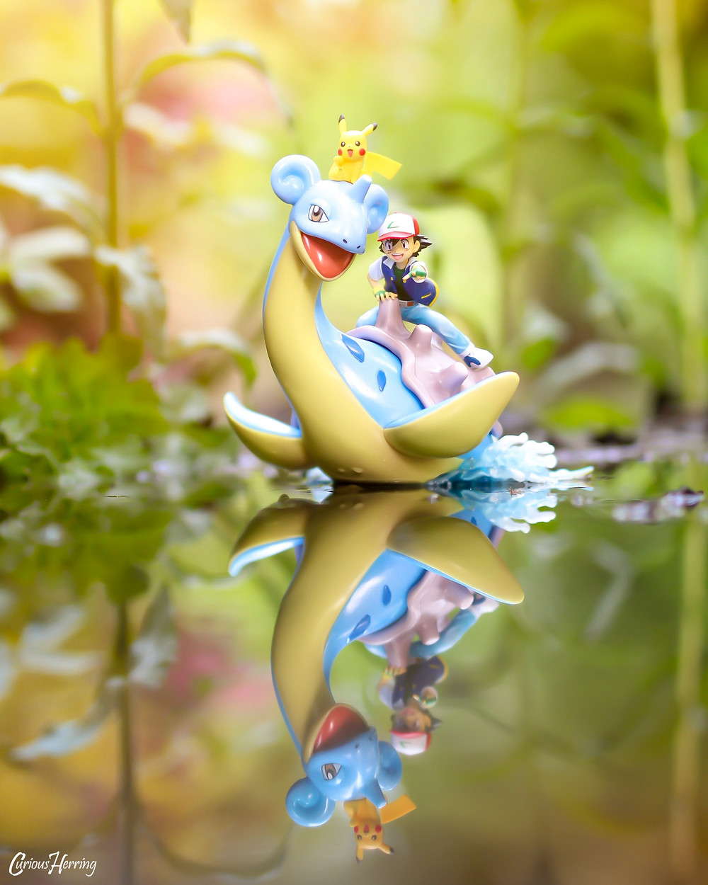 Toy Photography by CuriousHerring of Lapras, Ash and Pikachu swimming across the lake. This image features the G.E.M. Pokemon series statue from Nintendo, using soft focus to blur out the background, with a large focus on the figure and water reflection.