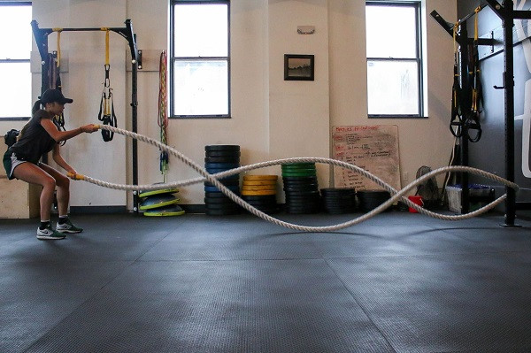 Lady using exercise rope- as used in personal training sessions