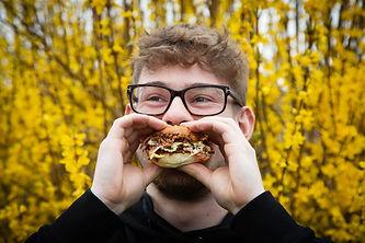 Guy enjoying eating a burger happy