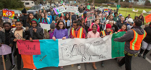 "A crowd of students of many different ages, genders, and races march down a street in Seattle, carrying signs. The students in front carry a red, blue, white, and green banner that says ""WE SHALL OVERCOME"" ""BLACK LIVES MATTER""."