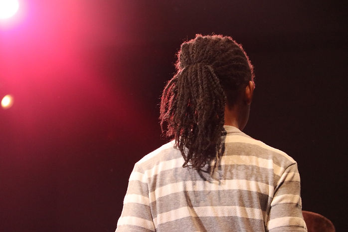 The back of ayoung Black person with locks in a ponytail and a grey and white striped shirton stage with warm red and yellow lights.