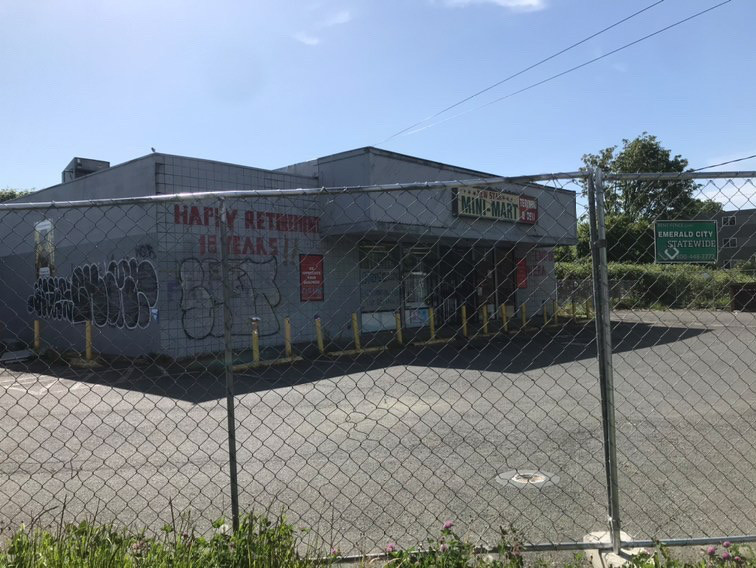 A street view of a closed minimart in South Seattle behind a chain link fence. The side of the building has some graffiti and written is HAPPY RETIREMENT 15 YEARS in red.