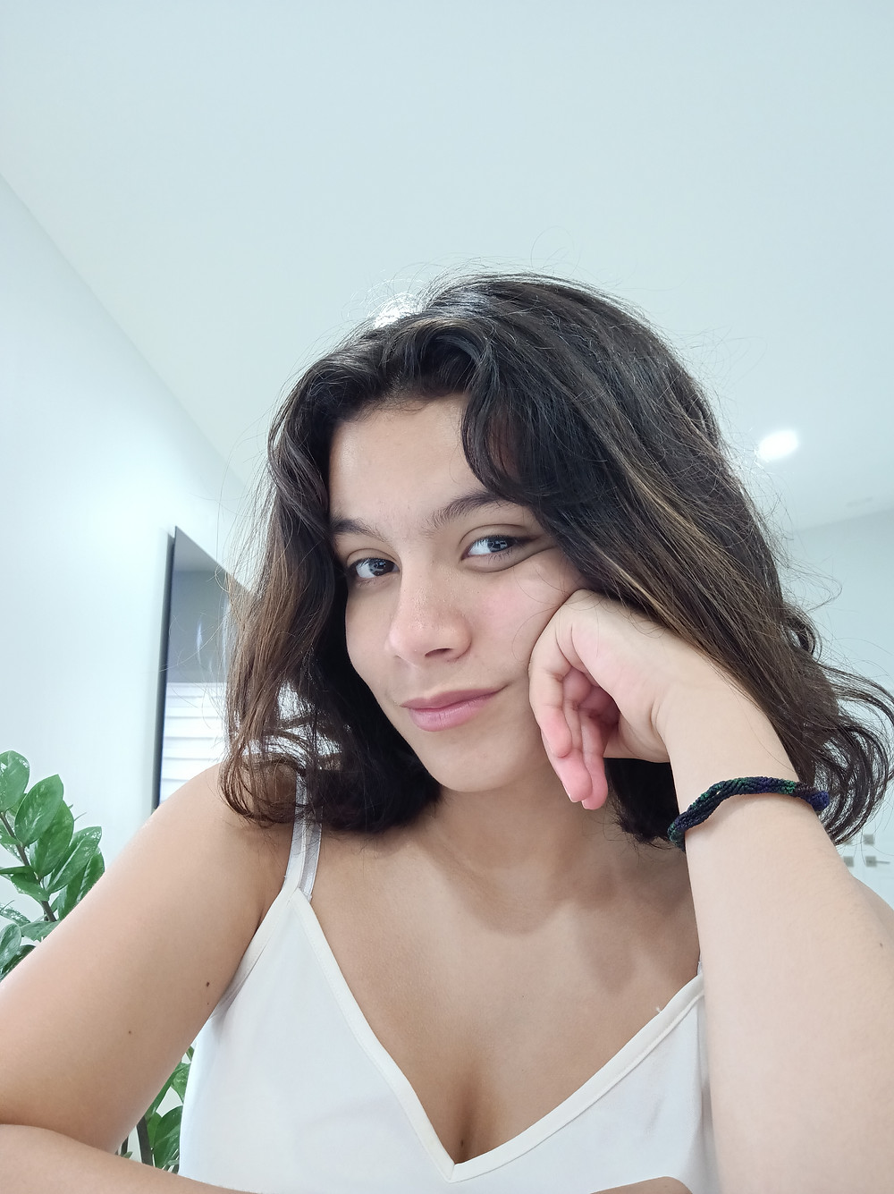 Amelie, a young latine person with shoulder length brown hair in a white tank top in a bright room, leaning against her hand looking at the camera.
