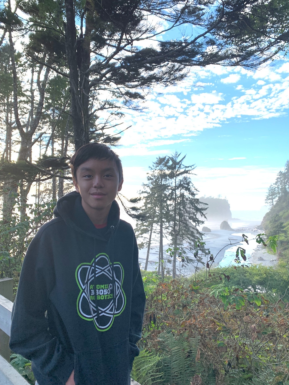 Ricardo, a Filipino young person with short black hair, stands in front of a forest and water landscape and sky with his hands in the pockets of a blue sweatshirt he's wearing.