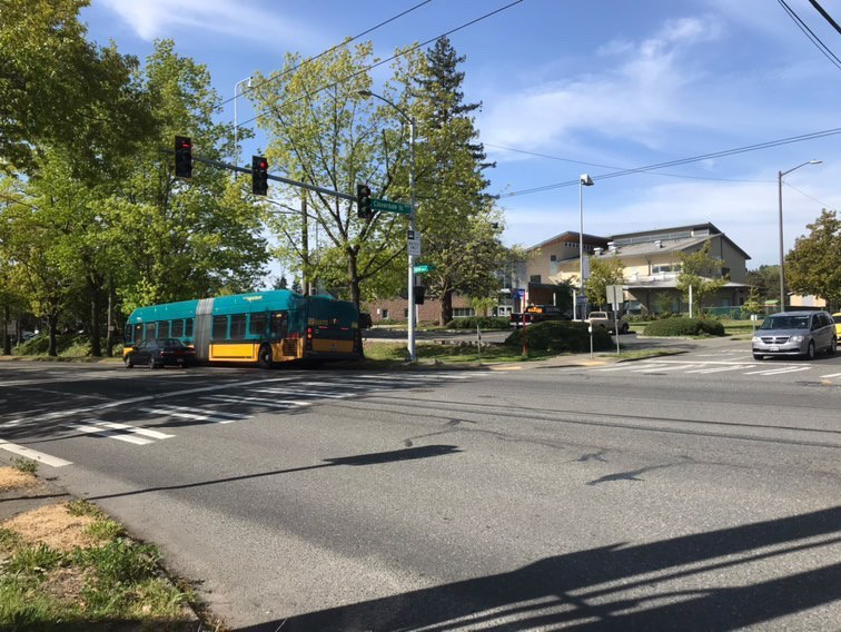 A street view of South Seattle at an intersection, a bus a few cars are passing by with trees and buildings in the background.