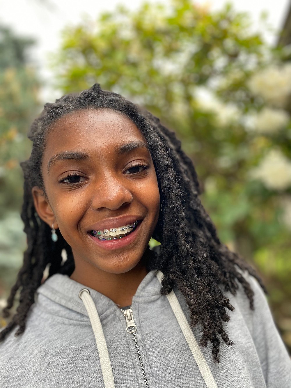 Heaven, an 11 year old Black girl with locs down to her shoulders and braces, grins at the camera with trees behind her in a grey sweatshirt.