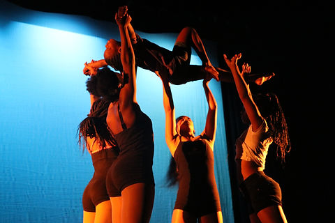 Four young people of color in black and white neutral clothing lift up another young POC who has one leg bent and one outstretched, their arms outstretched, and their head back. Warm stage lights light them in front of a light blue background.