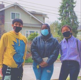 Three young people of color in face masks stand outside looking at the camera in front of a house and trees.