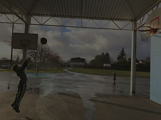 A young boy with an afro, dark sweatshirt and dark pants with a white strip, shoots a basketball midair on a basketball court on a playground with trees and houses in the background.