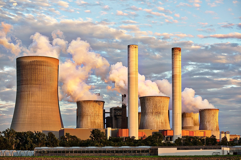 A power plant with multiple towers emitting lots of smoke in front of a partly cloudy sky.