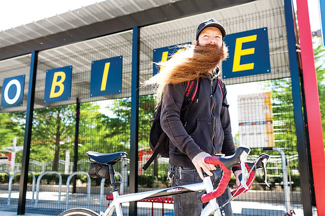 Caucasian man with a large beard standing in front of a Metrobike shelter walking his bike