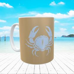 tan mug and blue crab
