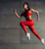 Young fit woman jumping while running Fi