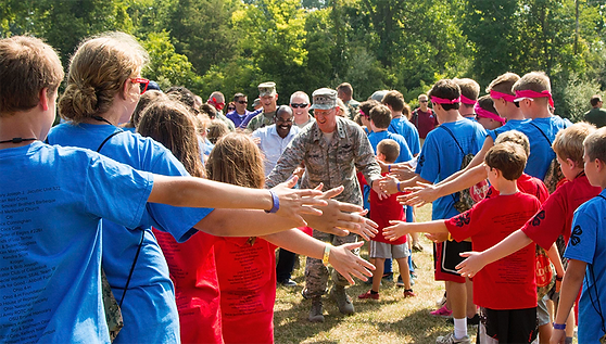smiling united states veterans walking through two sides of young people in red and blue t-shits touching hands as they go