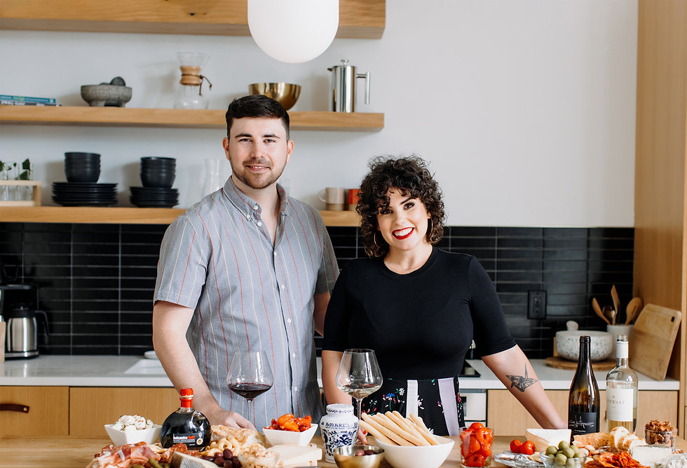 man and woman standing in their kitchen smiling at the camera