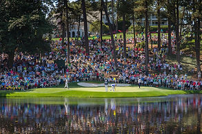 a large crowd overlooking a golf putting green behind a lake. consilium events.