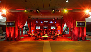 a red TV set with red furniture and wooden tables, with TV screens, red drapes and lighting. conslium experiential marketing agency.