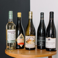 different bottles of wine standing on a wooden surface