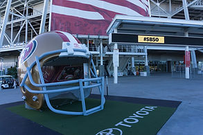 a very large football helmet on a green carpet in front of a stadium. consilium.