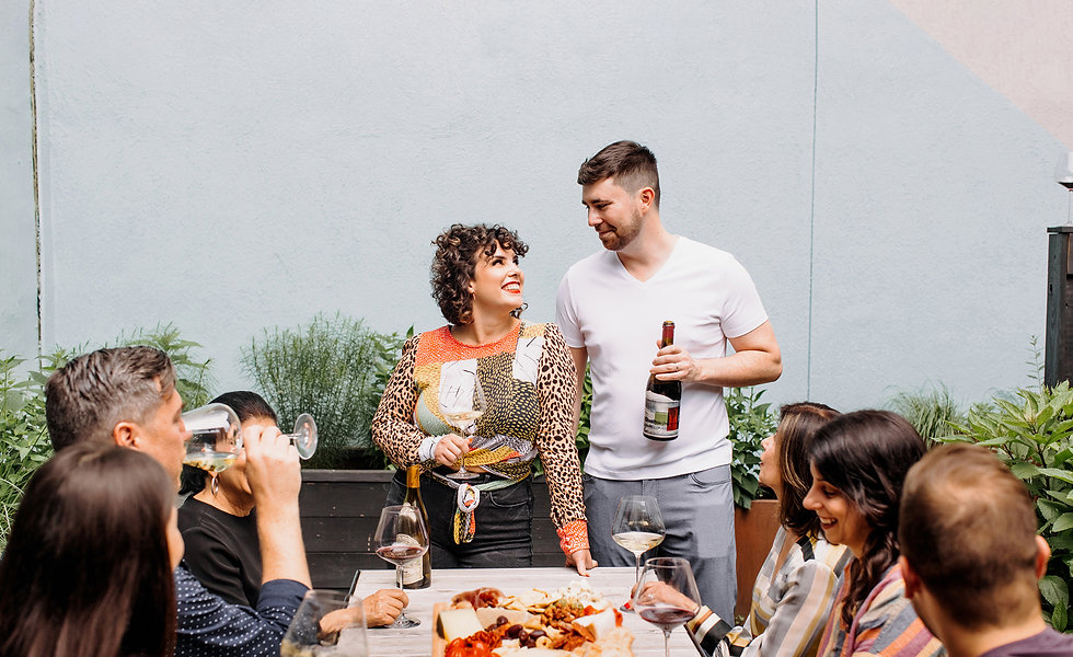 man and woman looking at each other smiling with their friends holding a wine glass and a bottle of wine
