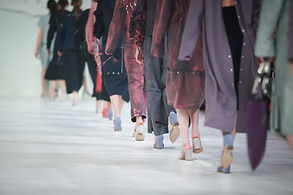 bottom half of women walking on a catwalk wearing various shades of purple and pink. consilum events.