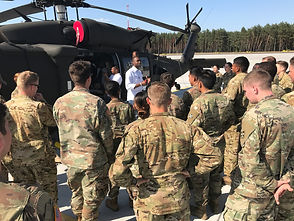 a group of military personnel listening to an african american gentleman speak in front of a helicopter. conslium experiential marketing agency.