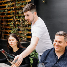 A man outside in a garden around a table with friends pouring wine to another man and woman