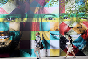 a man and woman walking past a billboard with three faces created from large colored squares. consilium experiential marketing agency.