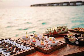 canapes and finger food on small plats on a wooden table overlooking the ocean at sunset. consilium events.