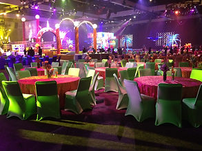 a large room set for a party decorated with lights, and in pink and green decor. consilium.