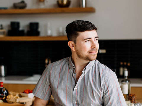 man with brown hair wearing a striped shirt looking away from camera