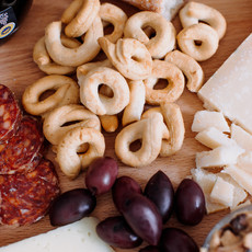 detail of a charcuterie board showing olives and meats, bread and cheeses