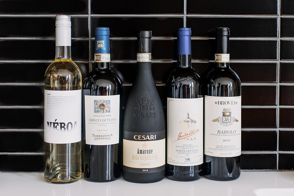 a selection of five different wines on a counter top in front of a black tiled wall