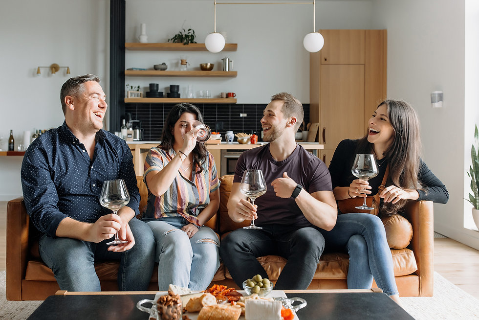 a group of friends, two women and two men, sitting on a couch laughing and drinking wine