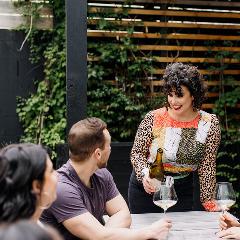 A woman standing at the head of a table watching other male and female friends trying wine sitting around a table outside in the garden