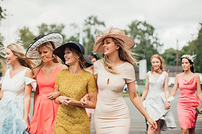 ladies wearing fancy dresses and hats. consilium events.