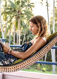 Kaila Krayewski, Founder of the Digital Nomad Writing Club, writing in a hammock