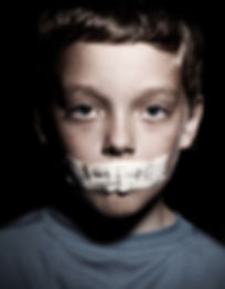 Young male child with tape over is mouth with the words help me written on it