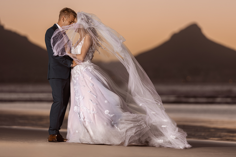 A very special Bride and Groom enjoying their first alone time together as newly weds on the beautiful Cape Town beach with Table Mountain in the back ground.