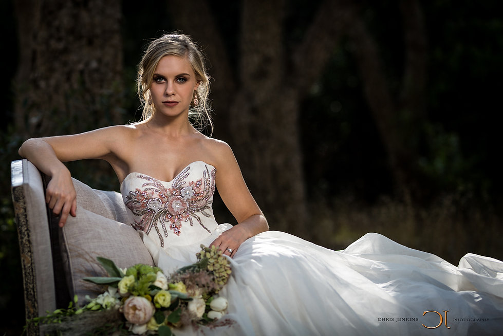 Beautiful bride in her wedding dress, sitting on a couch in the middle of a forest.