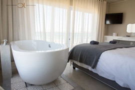 Blue Bay Lodge, Saldanha Bay, wedding venue with stunning large modern rooms. Clean white bedding and free standing batch with a view over the sea.
