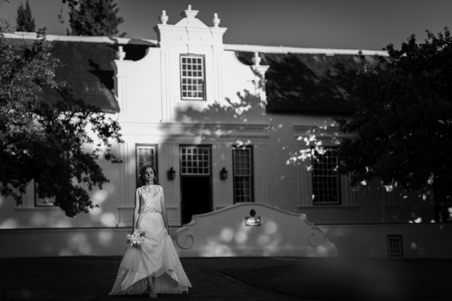 Beautiful bride in her wedding dress on her wedding day walking away from the manor house on the well-known Lanzerac Wine Estate in Stellenbosch, Cape Town. Edited with Brown and Autumn colours.