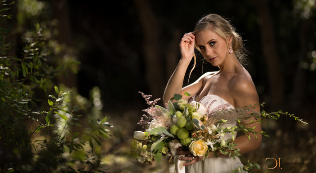 Beautiful bride in her wedding dress on her wedding day showing off her phenomenal bouquet in the forest of the well-known Lourensford Wine Estate, Somerset West, Cape Town. Edited with Brown Autumn colours.