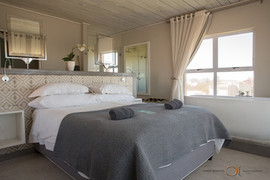 Blue Bay Lodge, Saldanha Bay, wedding venue with stunning large modern rooms. Clean white bedding and a view over the sea.