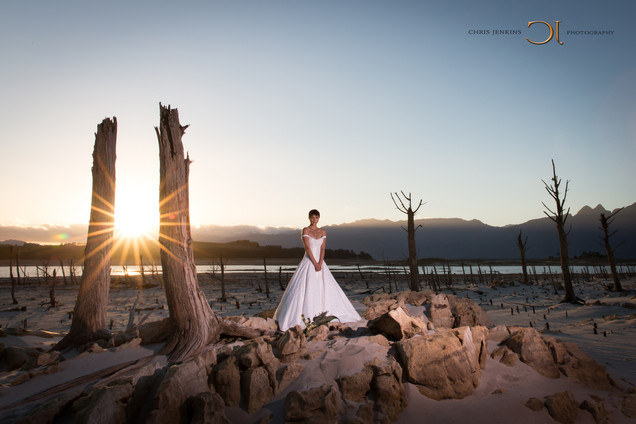 Beautiful bride in her wedding dress on her wedding day standing in the middle of the Karoo in the empty Theewaterskloof Dam with a lovely sunset as backdrop. Edited with Brown and Autumn colours.