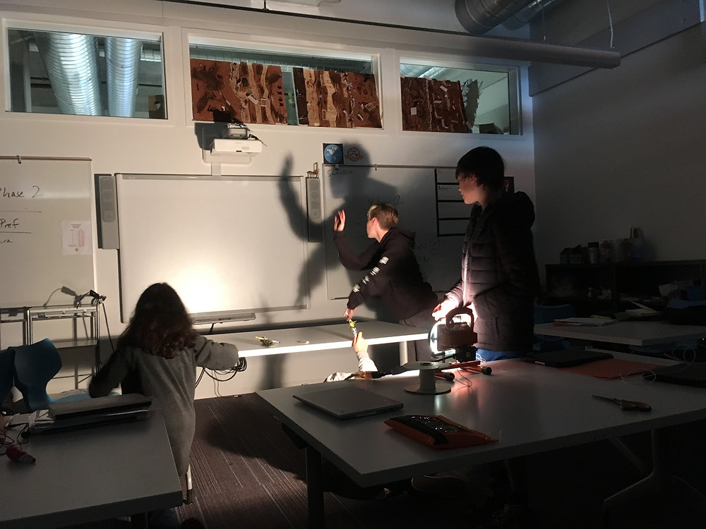 Students test prop shadows. Shadows are a key part of this allegory!