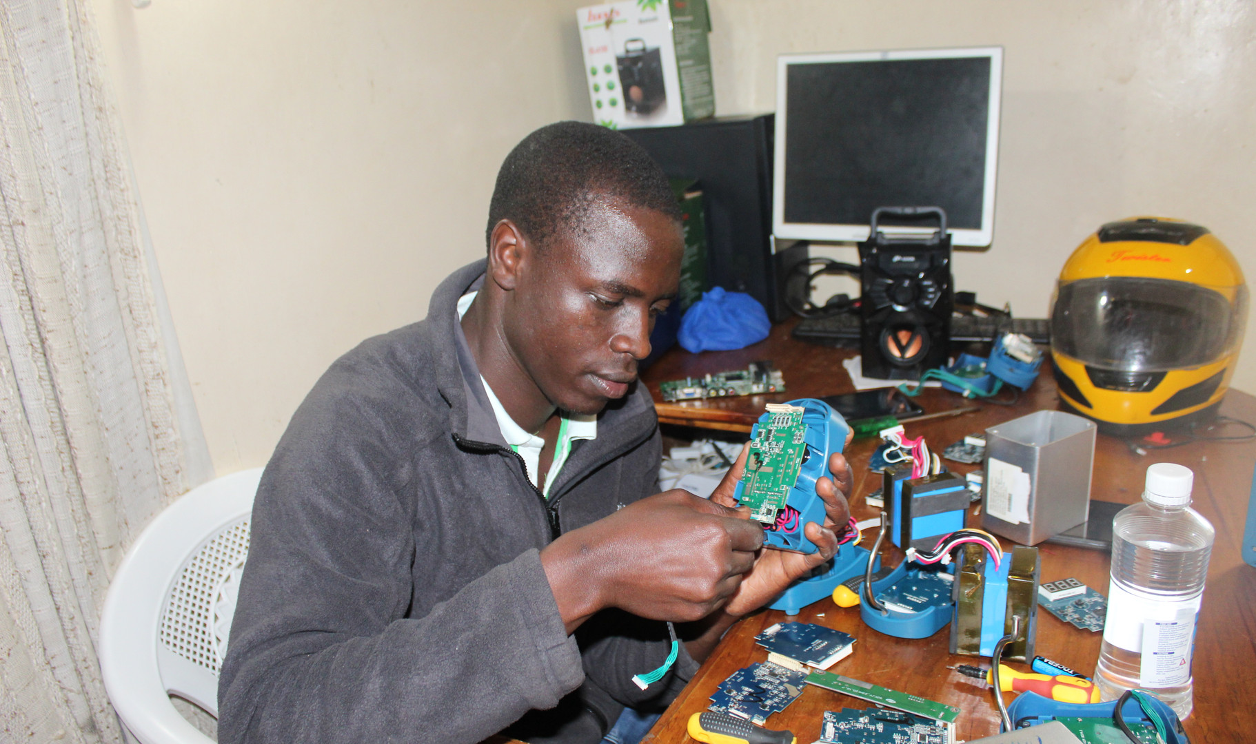 Eliud repairing a client's battery