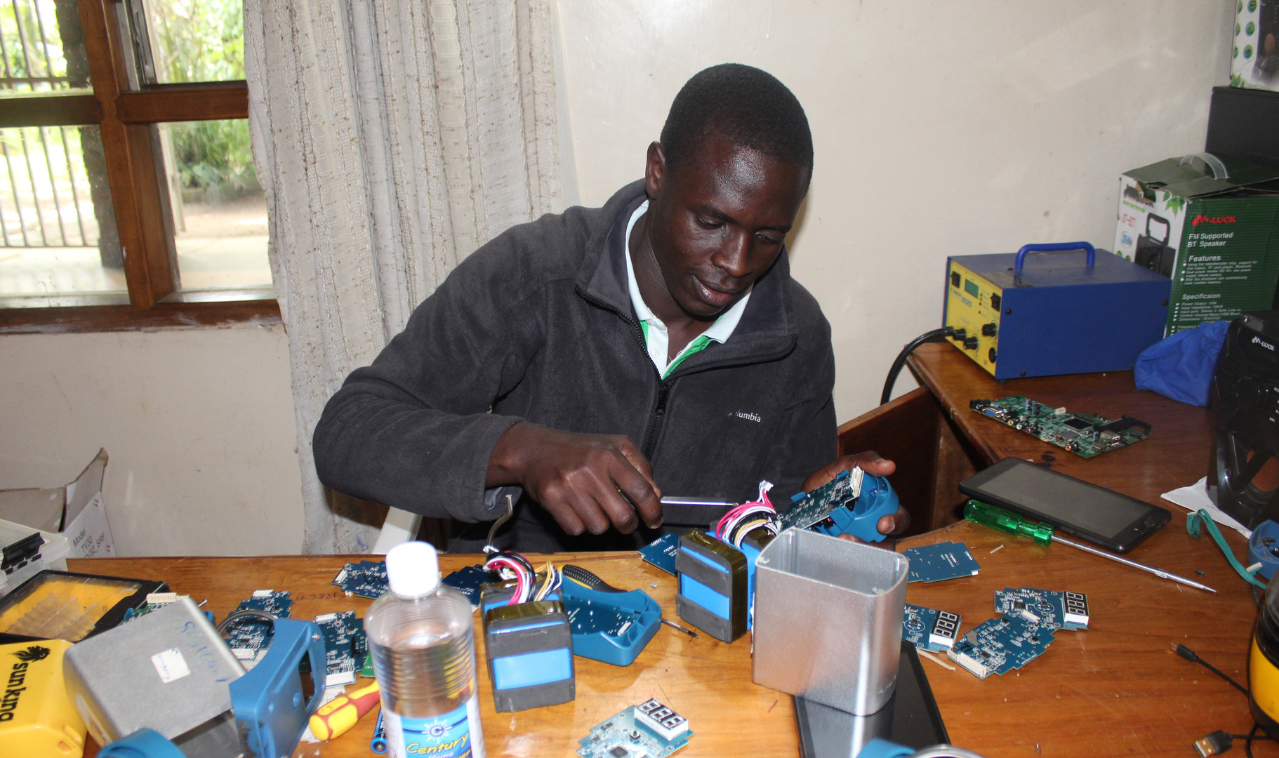 Technician, Eliud repairing a battery