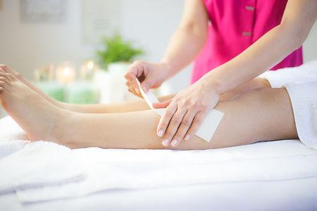 beautician waxing leg of clien